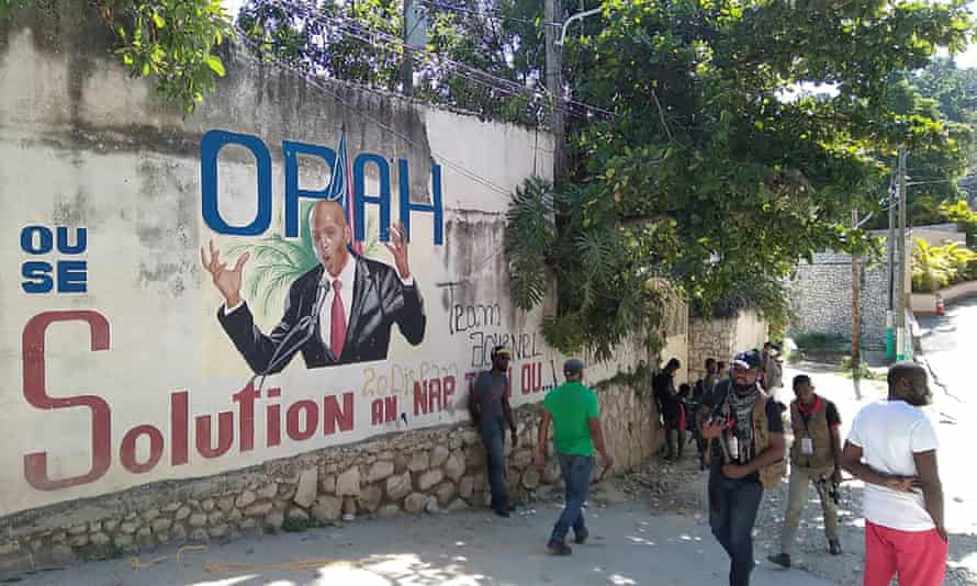 People walk past a wall in Port-au-Prince, Haiti, with a mural depicting President Jovenel Moïse