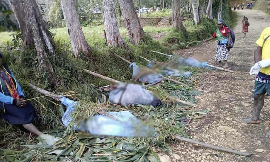 Villagers stand by the bodies of victims recovered from tribal violence in Karida, Papua New Guinea.