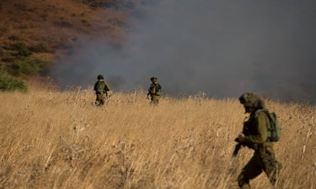 Israeli soldiers patrol next to a smoke from a fire caused by a rocket