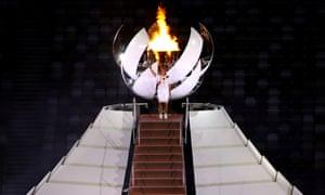 Naomi Osaka lights the Olympic cauldron in Tokyo.