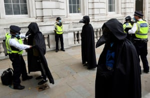 London, England Police officers search members of the Animal Rebellion group during an Extinction Rebellion protest