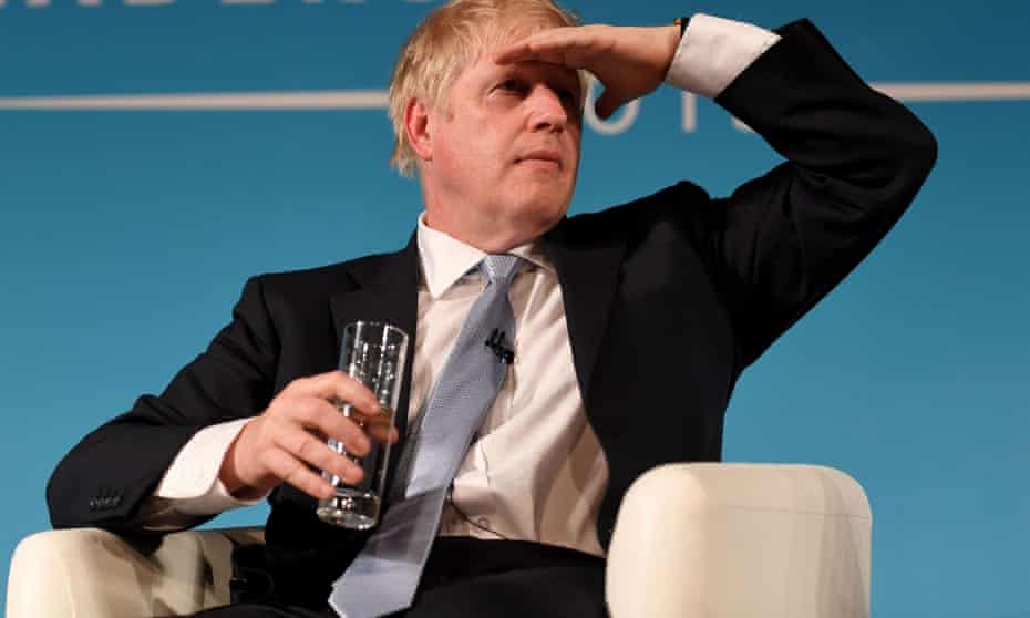 Boris Johnson shades his eyes with one hand, with a glass in the other.