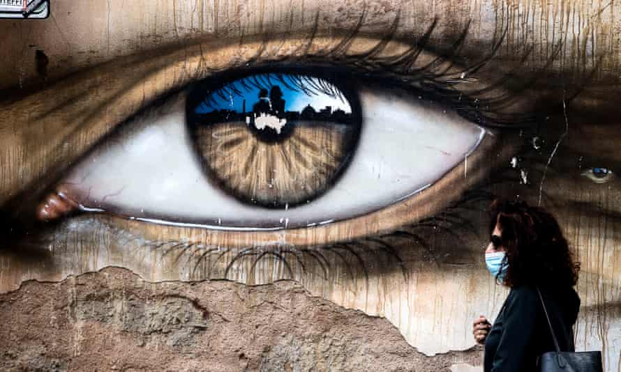 A person wearing a face mask walks in front of a mural of a large eye during the Covid pandemic in Italy, Rome.