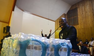 A pastor speaks to the crowd on a pedestal of bottled water during a town hall meeting in Flint, Michigan.