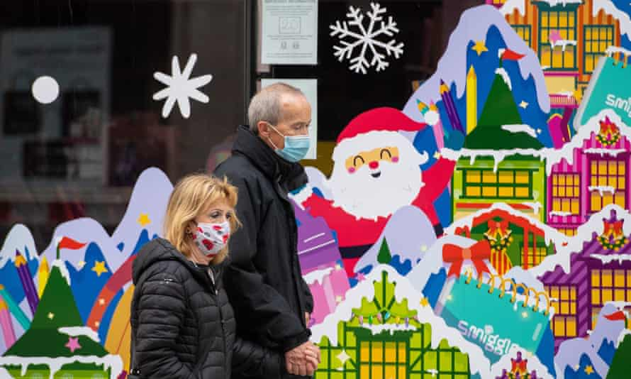 A man and a woman in face masks walk past a colourful shop window with a picture of Santa Claus in a snowy village