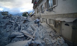 A man carries a pram among damaged buildings in Amatrice.