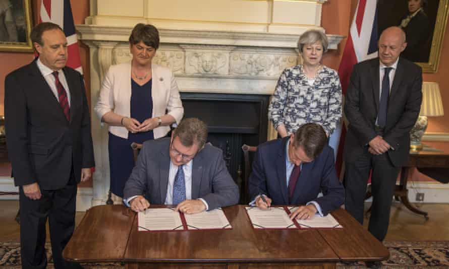 From left, Nigel Dodds, Arlene Foster, Theresa May and Damian Green watch Jeffrey Donaldson and Gavin Williamson sit and sign an agreement between the DUP and the Conservatives.
