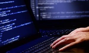 Hacker using a laptop running a computer programme