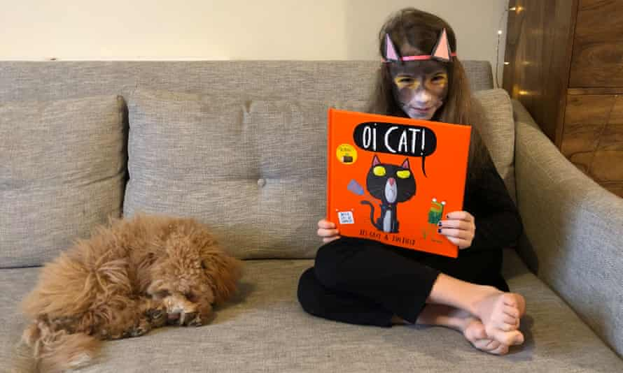Flora Ferguson, pictured with dog Rosie, enjoying Oi Cat! by Kes Gray and Jim Field.