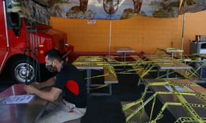 A man waits for his order at a food truck while dining tables are sealed off with caution tape in Los Angeles, California, on 1 July.
