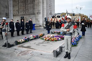 Soldiers stand next to the Tomb of the Unknown Soldier at the Arc de Triomphe