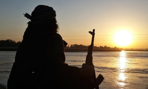 A Islamic State fighter looks over the Euphrates river in Raqqa, Syria.