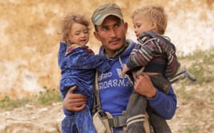 Deir Al Zor province, SyriaA fighter of Syrian Democratic Forces (SDF) holds two children in the village of Baghouz.