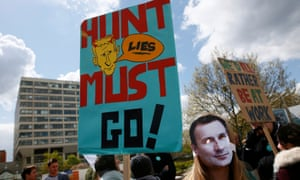 A junior doctor wears a mask bearing the face of Jeremy Hunt during a strike outside St Thomas' Hospital in London
