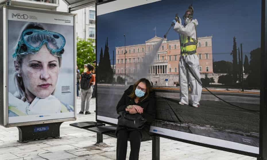 A woman waits at a bus stop in Athens on 4 May, the day Greece began easing its nationwide coroanvirus lockdown.