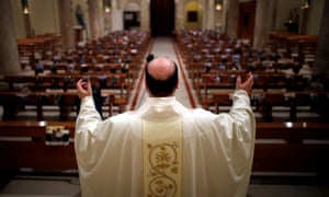 Priest Don Giancarlo Ruggieri gestures as he livestreams an Easter Sunday Mass from an empty church, with members of the congregation replaced by their photographs.