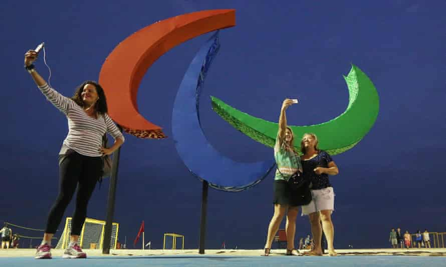 People take photos in front of the Paralympic symbol, Agitos, on Copacabana beach.