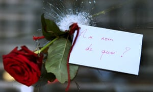 A note hangs from a rose placed in a restaurant window bullet hole in Paris