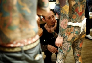 A man admires a person's tattoos at the annual gathering of the Irezumi Aikokai (Tattoo Lovers Association) in Tokyo.