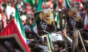 People hold posters during the funeral ceremony of Iranian general Qassem Suleimani in Tehran, Iran.