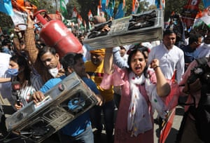 Delhi, India. Indian Youth Congress activists carry liquified petroleum gas cylinders during a protest against fuel and cooking gas price hikes