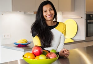Priya Basil in her kitchen, leaning on a counter with a bowl of fruit in front of her