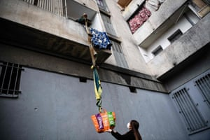 A resident of the White House estate collects food offered by neighbours from his balcony, using a rope made with blankets.