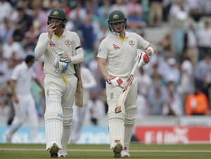 Steve Smith and Michael Clarke, wearing a black armband in memory of Australian cricketer Philip Hughes, walk back to the pavilion as play stops for afternoon tea.