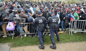 French police officers push back a large crowd of migrants lining-up at the processing centre.