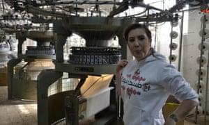 Tamara Alarja stands next to the fabric weaving machine inside her family factory in Palestine.
