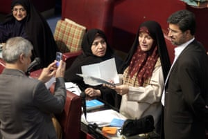 Fatemeh Haghighatjoo, who served as a reformist MP from 2000-2004, holding papers, poses for a lawmaker to take a photo after the parliament accepted her resignation.