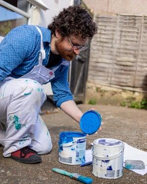 Tom Druker opening cans of paint.