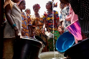 Fulani women wait their turn to retrieve a bucket of water in an internally displaced people's camp on the outskirts of Bamako, Mali.