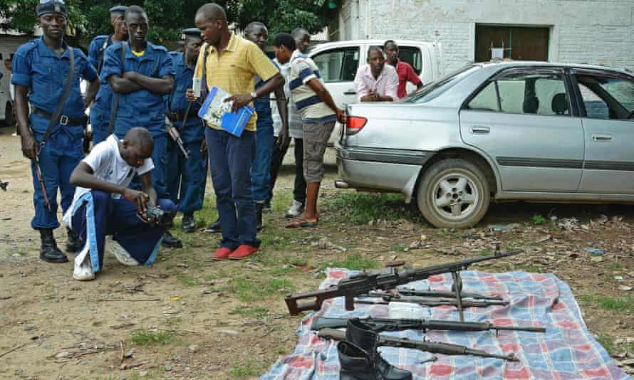 Journalists and police look at weapons seized in Bujumbura.
