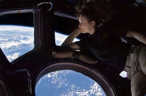 Astronaut Tracy Caldwell Dyson looks through a window in the Cupola of the International Space Station