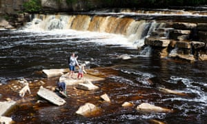 A woman with children and a dog enjoying the waters at the Richmond Falls, a dramatic series of waterfalls along the River Swale in Richmond, North Yorkshire.