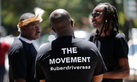 Three Uber drivers, in Uber t-shirts, in conversation outside the company's offices in Parktown, Johannesburg