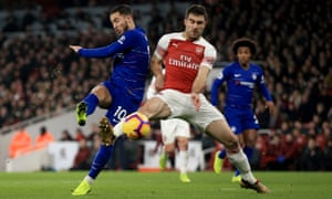 Eden Hazard of Chelsea shoots wide as Arsenal's Sokratis Papastathopoulos attempts to block.