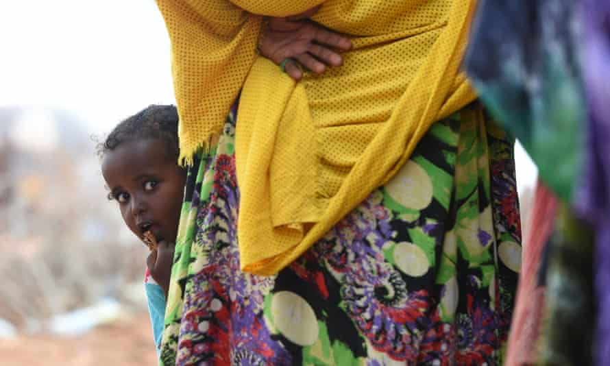 A child peers out from behind her mother as they wait for food aid in Gumar, Somaliland, where villagers are suffering form famine and drought.