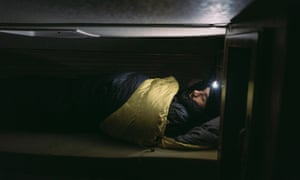 A man going to sleep in his camper and sleeping bag.