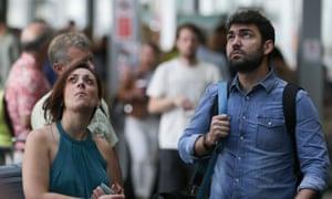 Passengers look at departure screens at London City airport