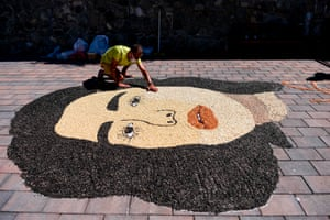 The artist Alkent Pozhegu works on a mosaic made with grains and seeds depicting the pop star Dua Lipa in Gjakova, Kosovo