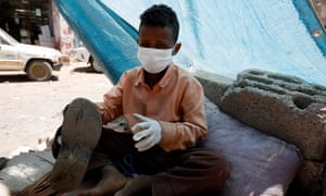 A child shoemaker wears a face mask and gloves to protect against Covid in Sanaa, Yemen