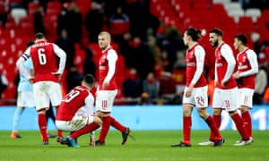Arsenal players gather at the final whistle but in the stands behind them at Wembley, most of their supporters had already left.