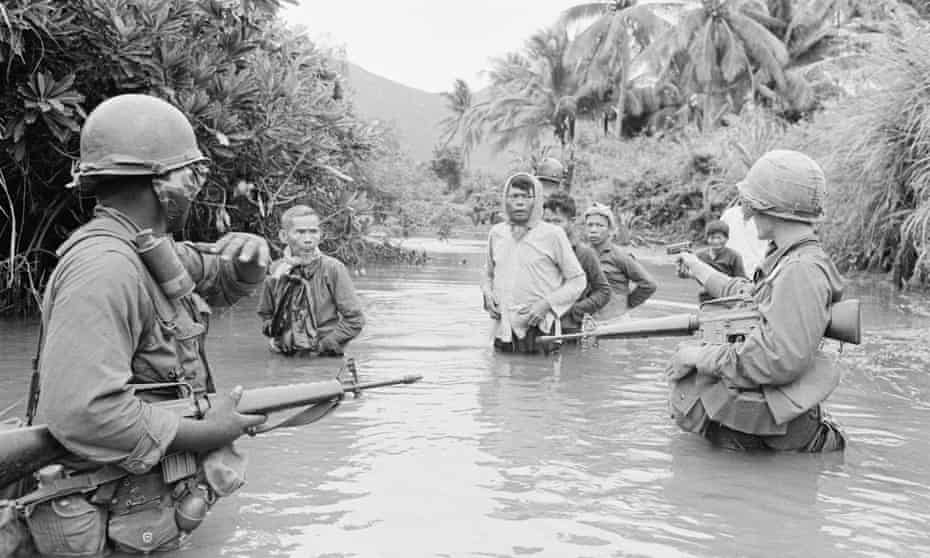 US troops move South Vietnam suspects across a stream, October 1966