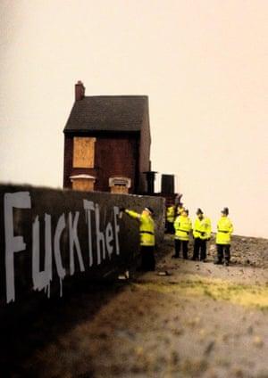 Policemen remove graffiti reading Fuck The P... in The Aftermath Dislocation Principle