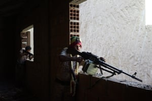 Two gunmen look down their gunsights from an upstairs window.