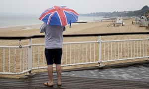 A man with a union jack umbrella looks on as rain falls at an empty Bournemouth beach, 3 June 2020.