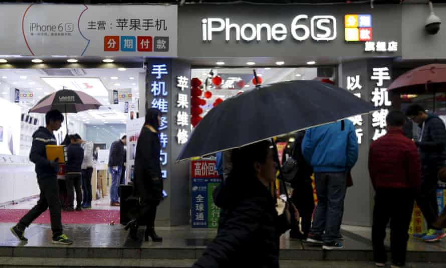 people walk past an iPhone shop in China
