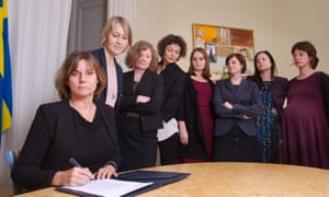 Flanked by colleagues, the Swedish deputy prime minister, Isabella Lövin, signs a bill.